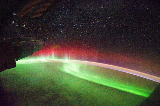 (Kuva NASA/Flickr, kuvateksti mukana) NASA image captured September 26, 2011 Many aurora appear green, but sometimes — as in this image from the International Space Station — other colors such as red can appear. The colors depend on which atoms are causing the splash of light seen in the aurora. In most cases, the light comes when a charged particle sweeps in from the solar wind and collides with an oxygen atom in Earth's atmosphere. This produces a green photon, so most aurora appear green. However, lower-energy oxygen collisions as well as collisions with nitrogen atoms can produce red photons -- so sometimes aurora also show a red band as seen here. Karen Fox NASA's Goddard Space Flight Center Credit: NASA